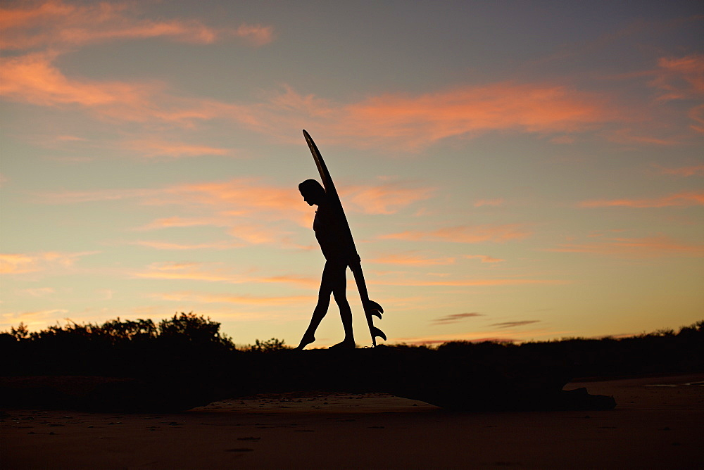 Silhouette female surfer with surfboard on beach at dusk