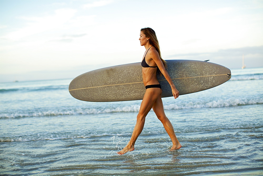 Female surfer carrying surfboard in ocean surf