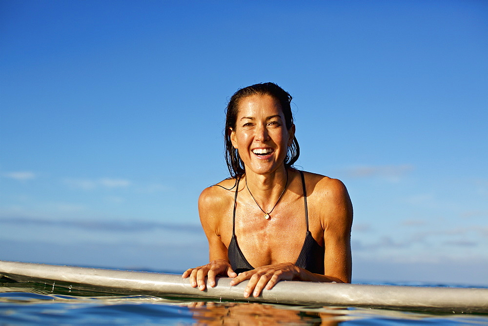 Portrait happy, confident female surfer leaning on surfboard in ocean