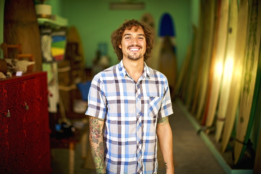 Portrait confident, happy male surf shop owner