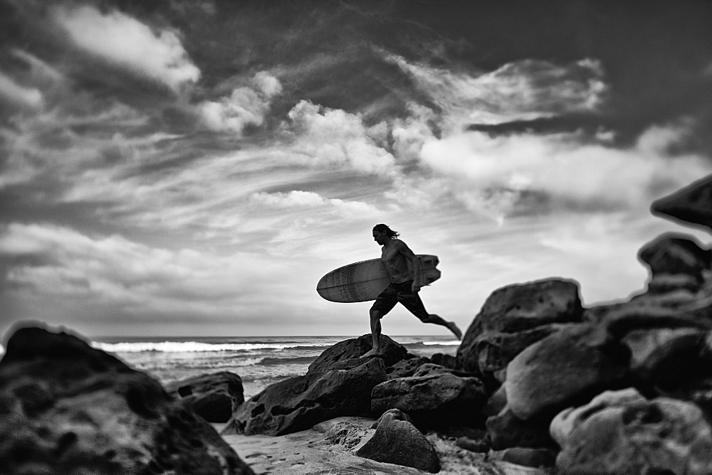Male surfer with surfboard on rocky ocean beach, Higuera Blanca, Nayarit, Mexico