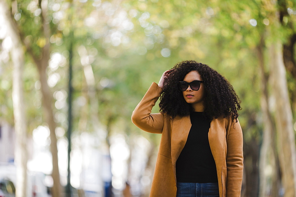 Stylish young woman in sunglasses walking in park