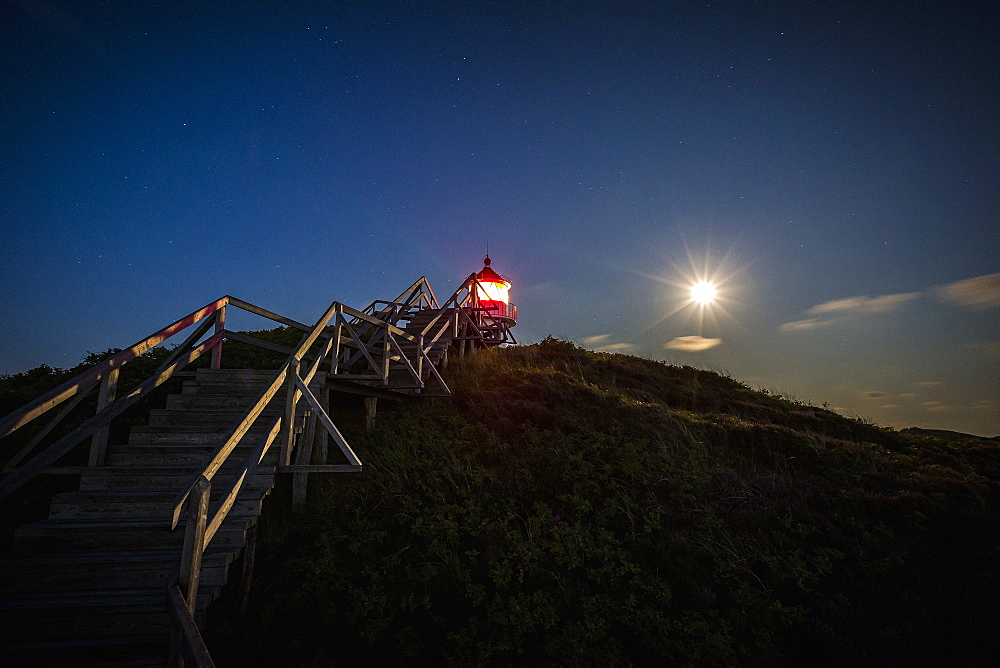 Illuminated lighthouse under full moon night sky, Norddorf, Schleswig Holstein, Germany