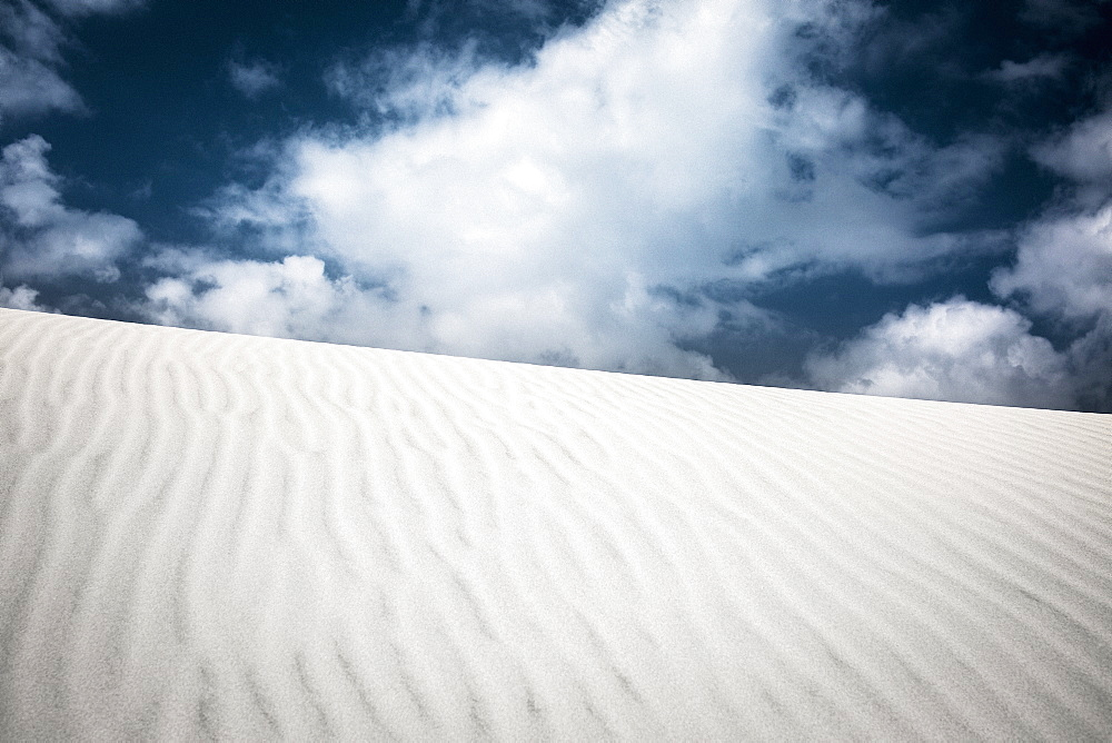 Pattern over sand dune below clouds in sky