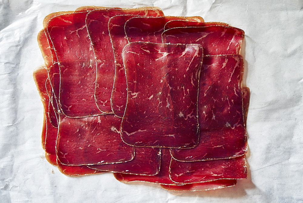 View from above sliced, air-dried Buendnerfleisch meat on butcher paper