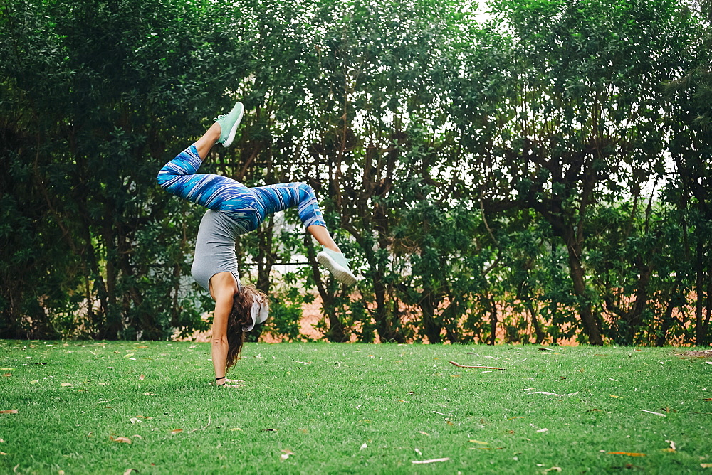 Fit, carefree female personal trainer doing handstand in park