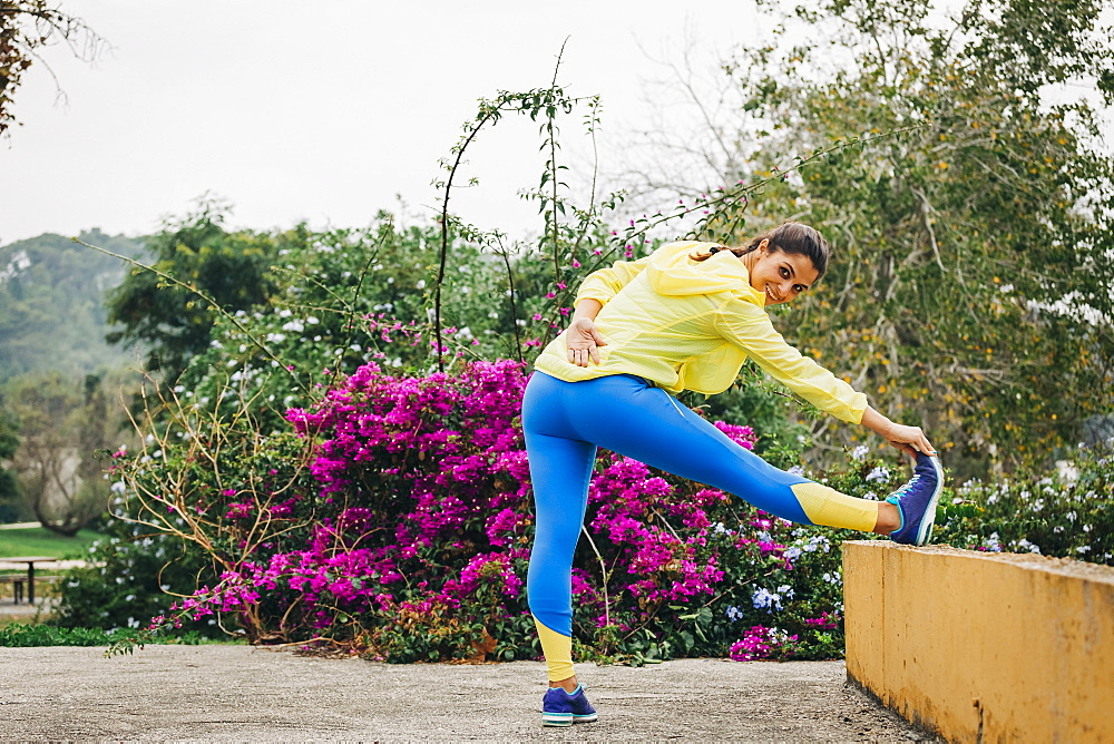 Portrait fit female personal trainer exercising, stretching leg in park
