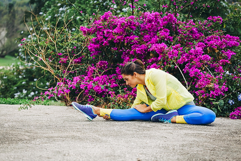 Fit female personal trainer exercising, stretching in park