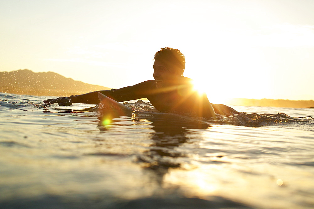 Happy male surfer paddling out on sunny, sunset ocean