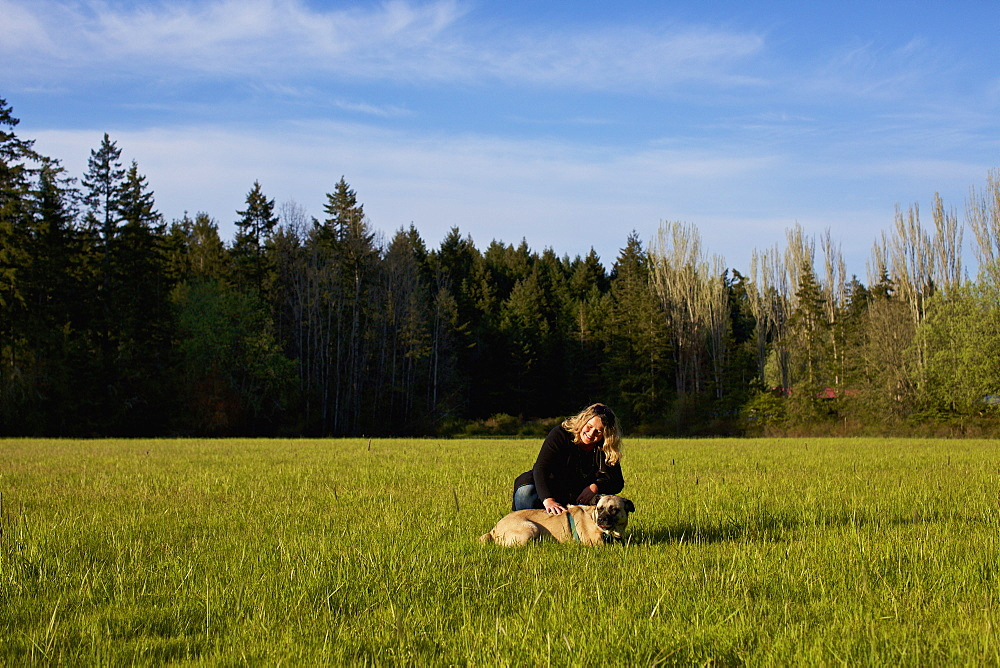 Woman with dog in sunny, rural field