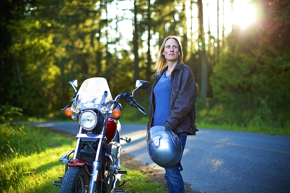 Confident woman standing at motorcycle at roadside in woods
