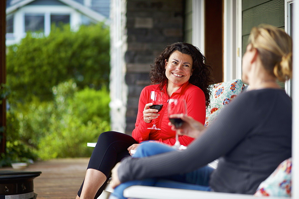 Happy women talking and drinking red wine on front porch