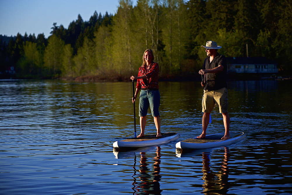 Couple standup paddleboarding on sunny lake, Shawnigan Lake, British Columbia, Canada