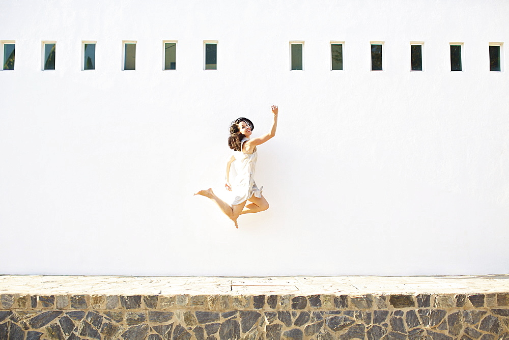 Portrait happy, carefree woman jumping for joy against sunny summer wall