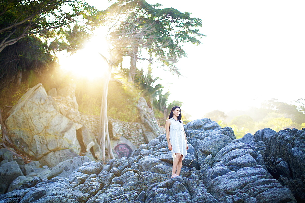 Serene woman standing on rocks under sunny tree, Sayulita, Nayarit, Mexico