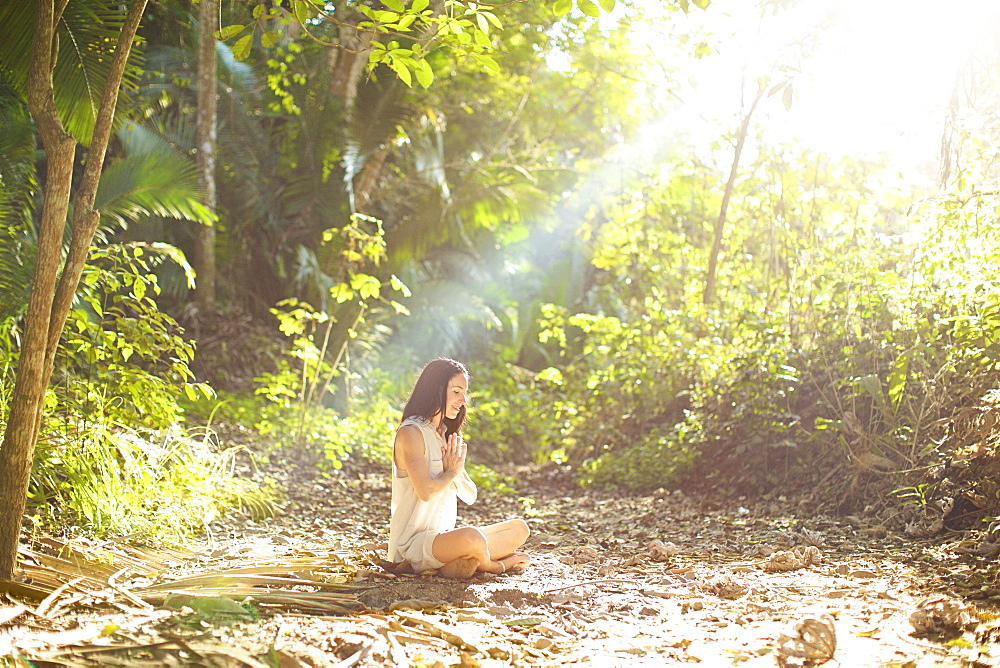 Serene woman meditating in sunny, tranquil woods, Sayulita, Nayarit, Mexico