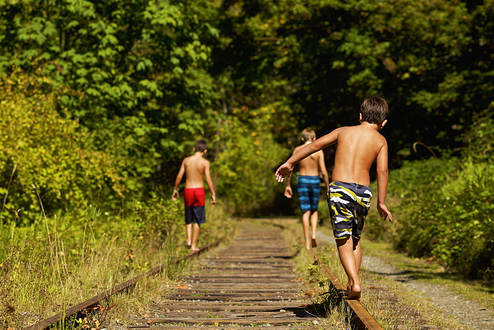 Boys in swim trunks walking along sunny railroad tracks in woods