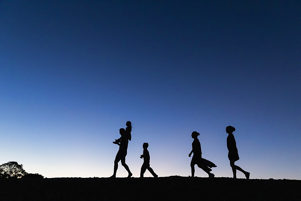 Silhouette family walking against blue sky at dusk