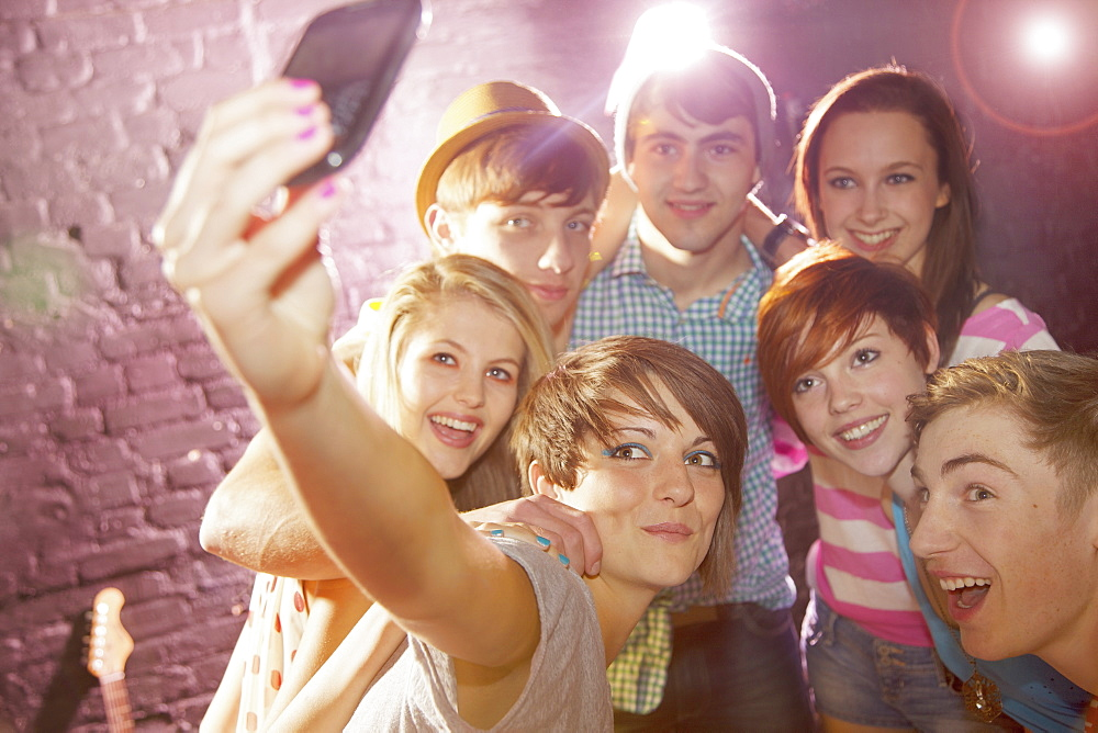 Happy teenage friends taking selfie at party