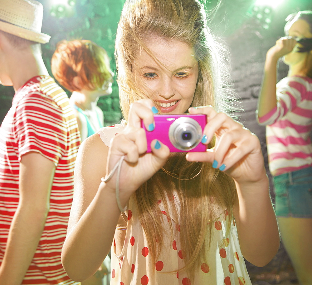 Playful teenage girl using digital camera at party
