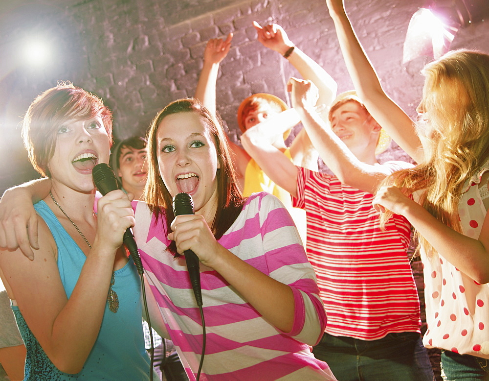 Happy teenage friends singing karaoke at party