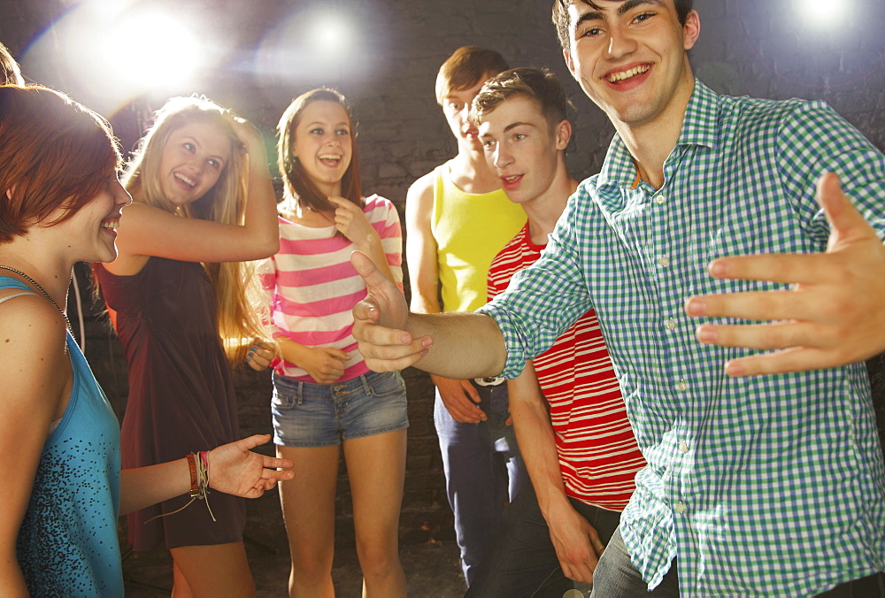 Happy teenage friends dancing at party