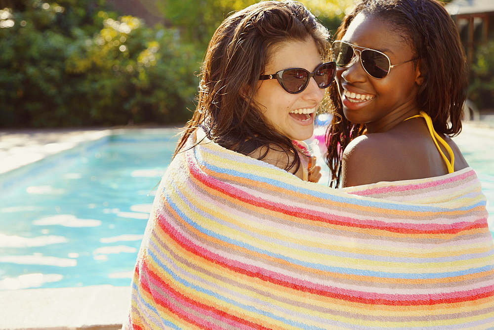 Portrait happy teenage girl friends wrapped in towel at summer poolside