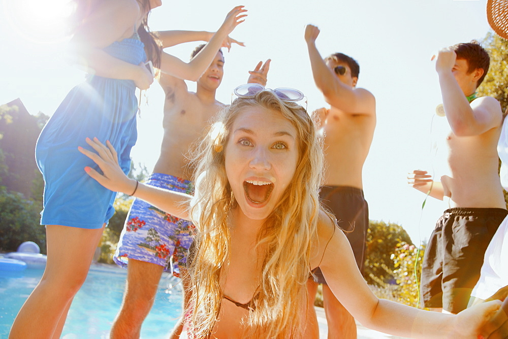 Portrait exuberant teenage girl dancing with friends at sunny summer poolside - 1177-3454