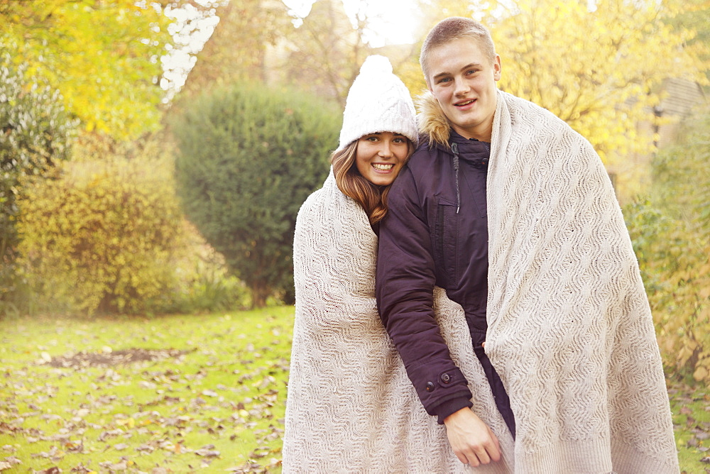 Portrait happy teenage couple wrapped in blanket in autumn park - 1177-3481