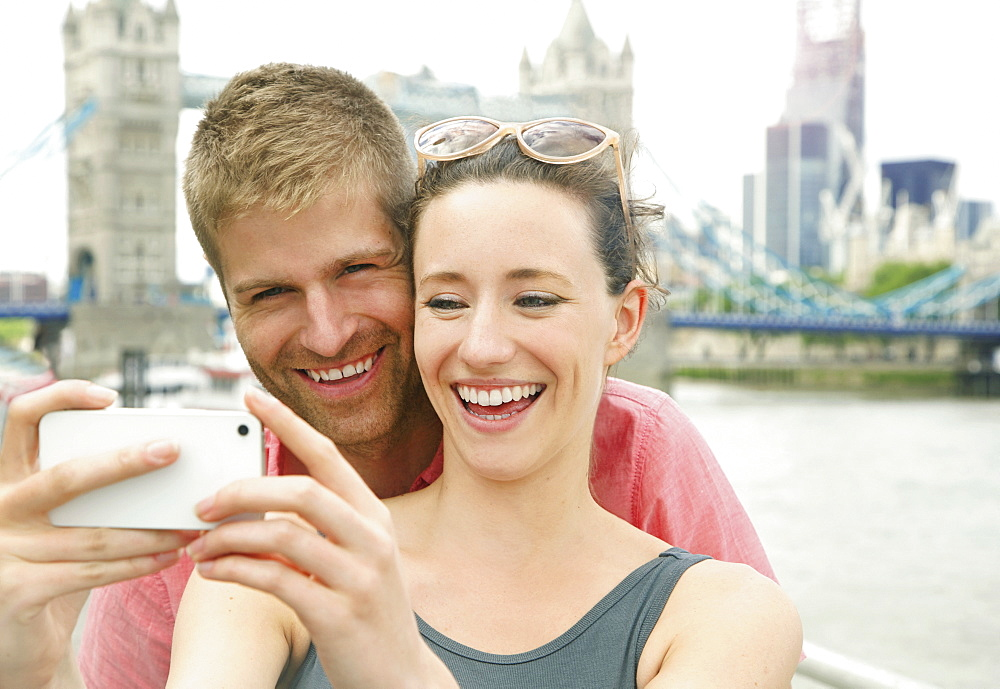Happy couple taking selfie with camera phone in front of Tower Bridge, London, UK