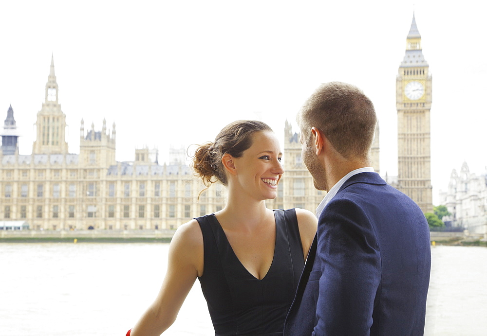 Happy couple standing in front of Thames River and Big Ben, London, UK
