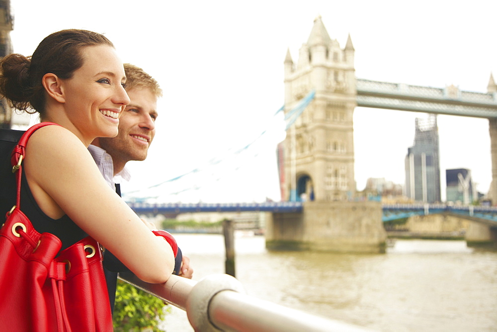 Happy young couple enjoying view of Thames River and Tower Bridge, London
