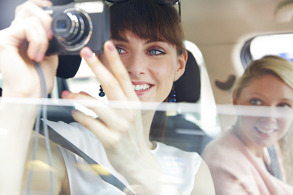 Happy young woman using digital camera from car window