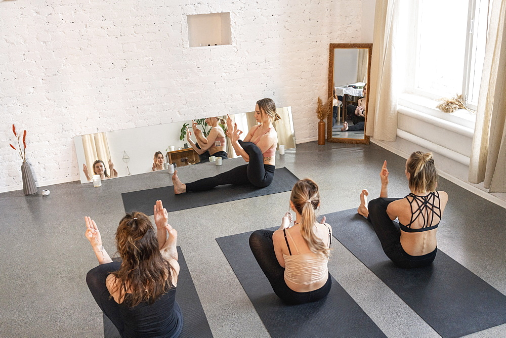 Yoga instructor and students practicing in yoga studio