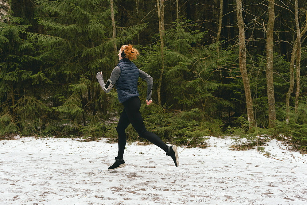 Woman running in snowy woods