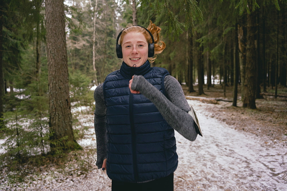 Portrait confident woman running in snowy woods - 1177-3567