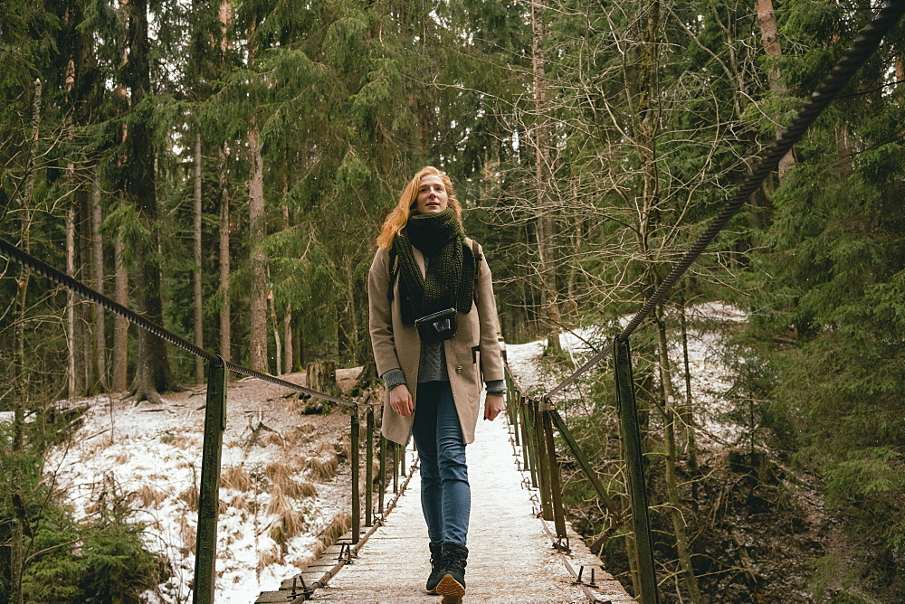 Woman in wool coat and scarf walking on footbridge in snowy woods