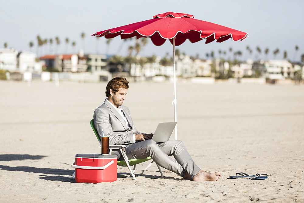 Barefoot businessman using laptop on sunny beach, Los Angeles, California