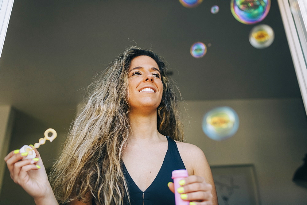 Happy young woman blowing bubbles in doorway