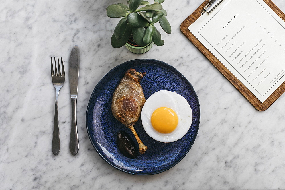 Confit duck leg and fried duck egg on restaurant table
