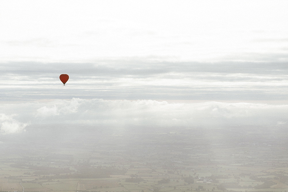 Red hot air balloon in sunny cloudy sky above Bath, Somerset, UK