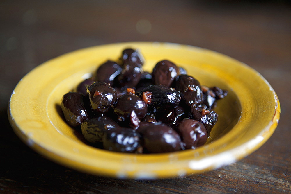 Close-up of marinated black olives in plate