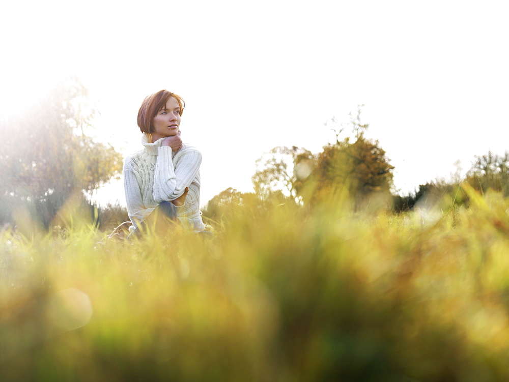 A woman sitting in the grass, looking away, low angle view