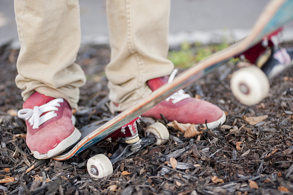 Low section of man with skateboard outdoors