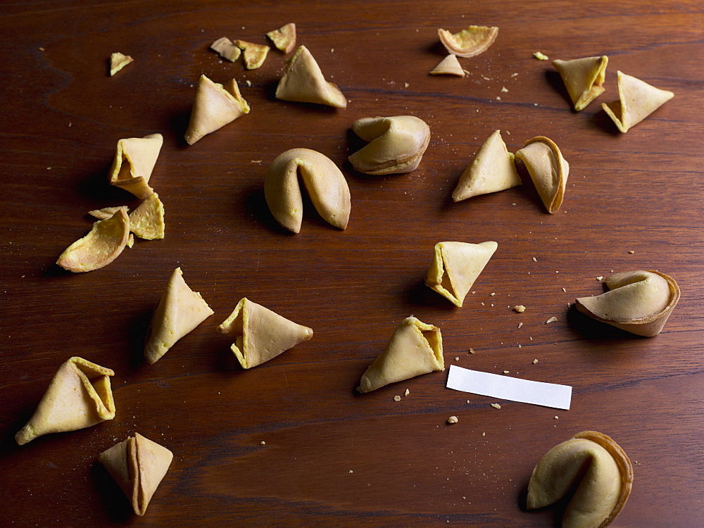 Fortune cookies and blank paper on wooden table