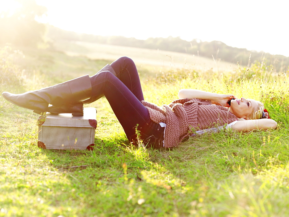 A woman lying in grass using a mobile phone - 1177-58