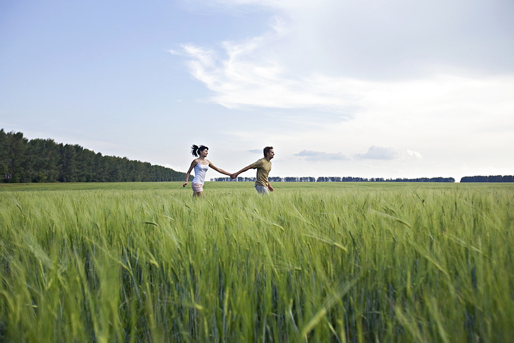 A man and woman holding hands and running through a wheat field