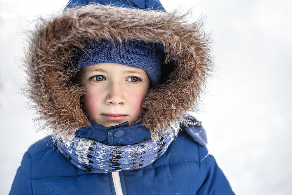 Thoughtful boy in warm clothing looking away outdoors
