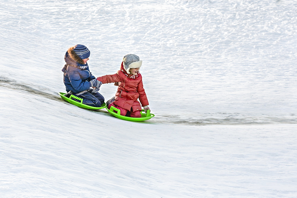 Full length of siblings tobogganing together in snow