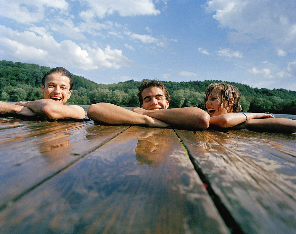 Friends resting on a wooden jetty